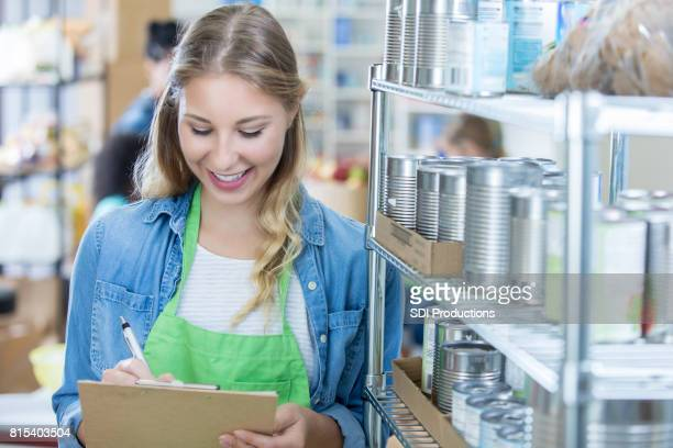 Confident female volunteer checks inventory food bank