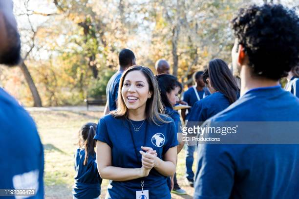confident female volunteer talks with friends - non profit organization stock pictures, royalty-free photos & images