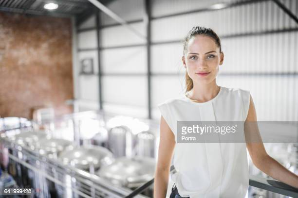 Confident female worker standing at brewery