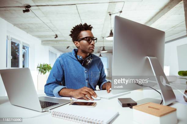 confident financial advisor using computer at desk - izusek stock pictures, royalty-free photos & images