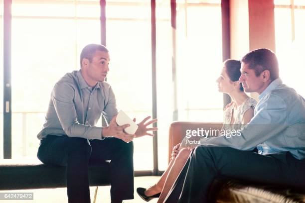 Confident financial planner talking to couple