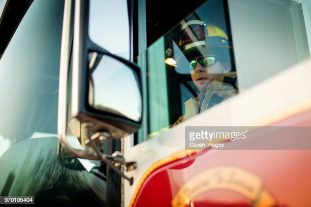 confident firefighter sitting in fire engine - capacete de bombeiro - fotografias e filmes do acervo