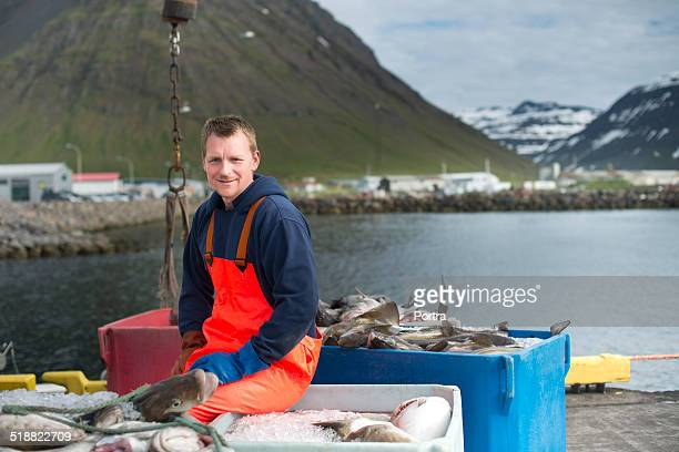 Confident fisherman sitting at industry