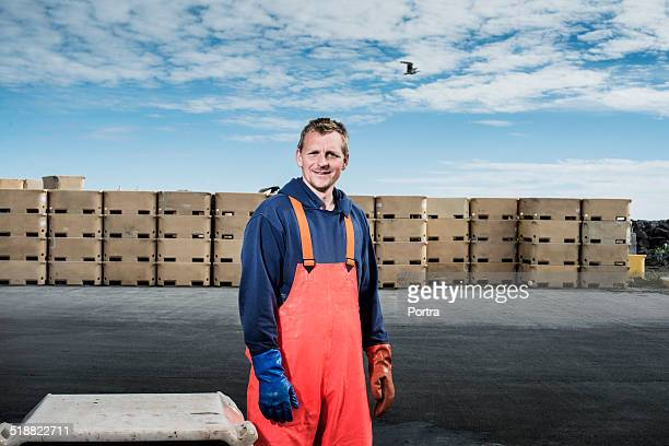 Confident fisherman standing at industry