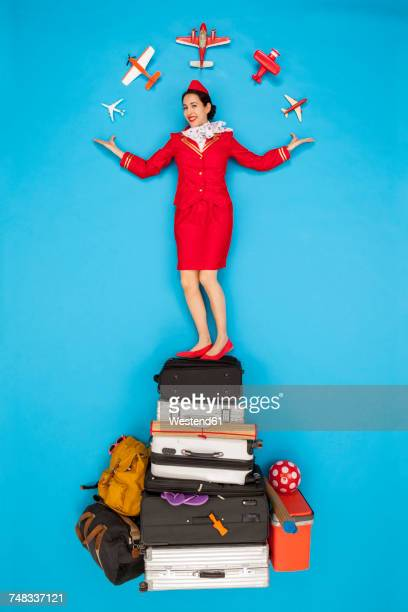 confident flight attendant standing on pile of luggage - reportaje imágenes stock pictures, royalty-free photos & images