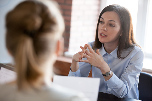Confident focused businesswoman speaking to people at business negotiations 1061027768