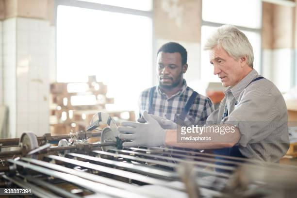 confident foreman explaining printing machine mechanism - printing press stock pictures, royalty-free photos & images