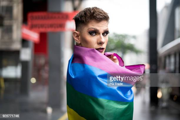 confident gay boy holding rainbow flag - androgynous stock pictures, royalty-free photos & images