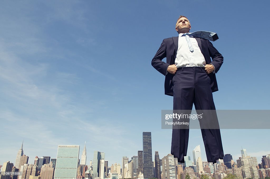 Confident Giant Businessman Standing Tall Over City Skyline : Stock Photo