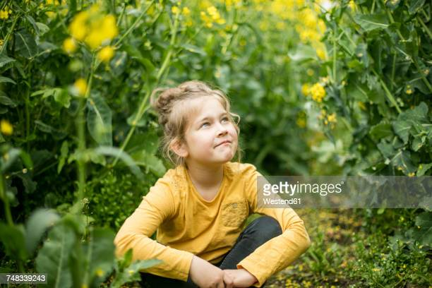 Confident girl sitting in rape field