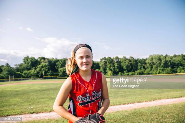 confident girl standing on baseball field on sunny day - baseball strip stock pictures, royalty-free photos & images