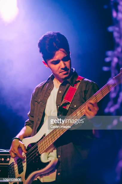 confident guitarist playing guitar in illuminated nightclub - guitarist stock pictures, royalty-free photos & images