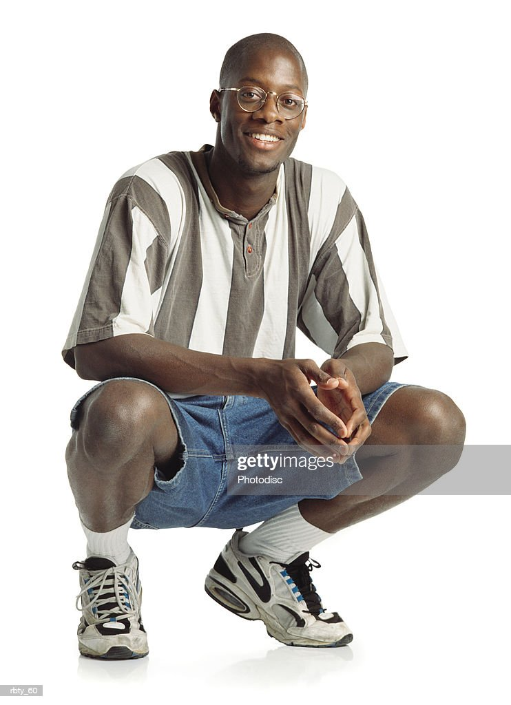 confident handsome african american young man wearing glasses and a striped shirt and jeans short squats down while smiling into the camera : Foto de stock