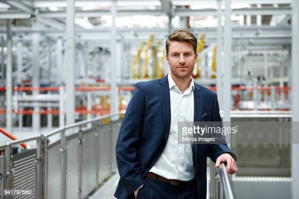 confident handsome businessman standing at factory - three quarter length stock pictures, royalty-free photos & images