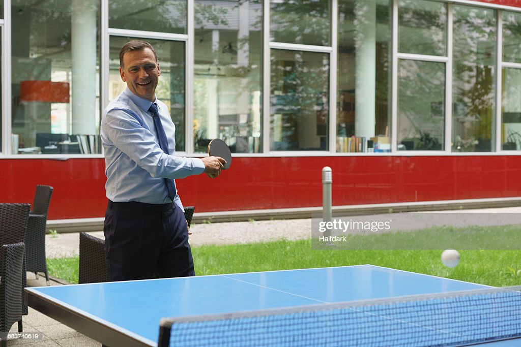 Confident happy businessman playing table tennis at creative office : Stock Photo