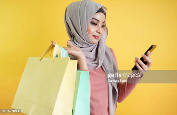 confident happy smiling muslim woman use mobile application to buy and shopping online product.. portrait of islamic customer woman hand holding shopping bag isolated over yellow background - modest clothing stock pictures, royalty-free photos & images