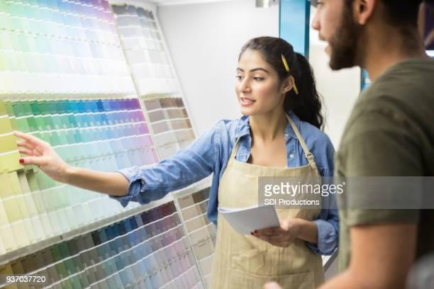 Vendedor de loja de ferragens confiante ajudando cliente