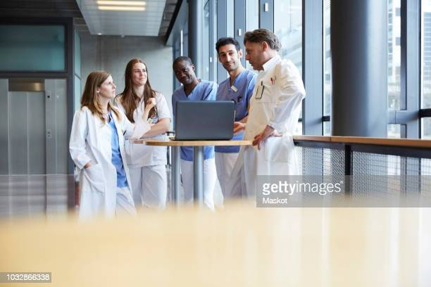 Confident healthcare workers discussing over laptop on table in corridor at hospital