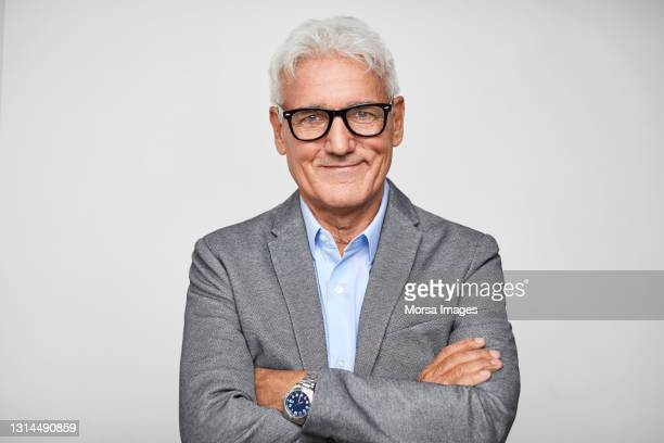 confident hispanic businessman against gray background - white hair stock pictures, royalty-free photos & images