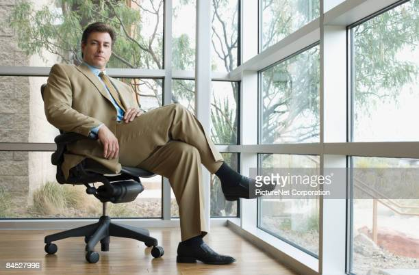 confident hispanic businessman sitting in chair - arrogance stock pictures, royalty-free photos & images