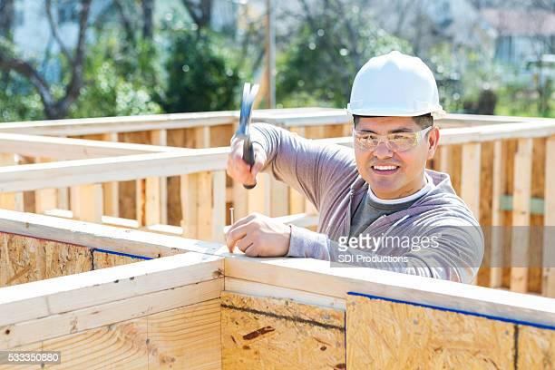 Confident Hispanic construction worker at job site