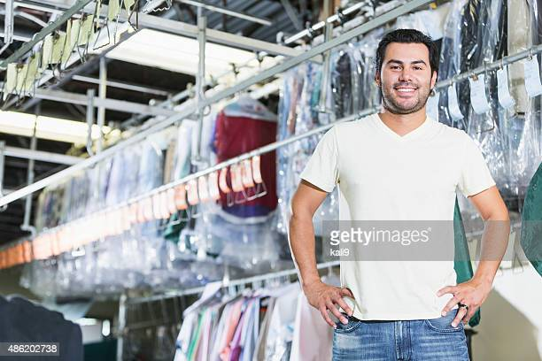 confident hispanic man working in dry cleaning store - man wrapped in plastic stock pictures, royalty-free photos & images