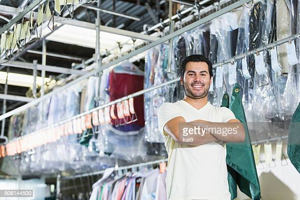 confident hispanic man working in dry cleaning store - dry cleaner stock pictures, royalty-free photos & images