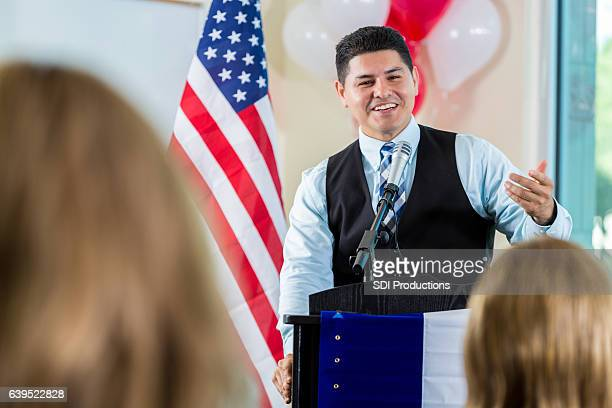 confident hispanic politician addresses supporters during rally - town hall meeting stock photos and pictures