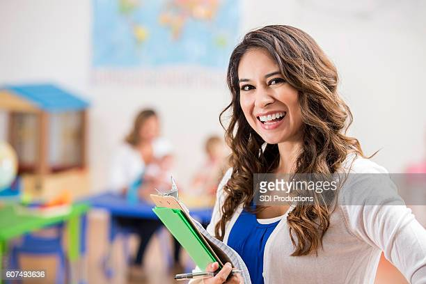 Confident Hispanic preschool teacher in class