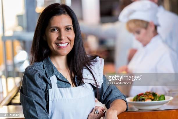 Serveuse de hispanique confiante dans la cuisine du restaurant
