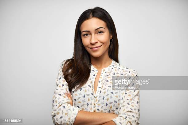 confident hispanic woman against gray background - business stock pictures, royalty-free photos & images