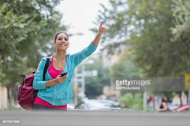 Confident Hispanic woman hails taxi in the city