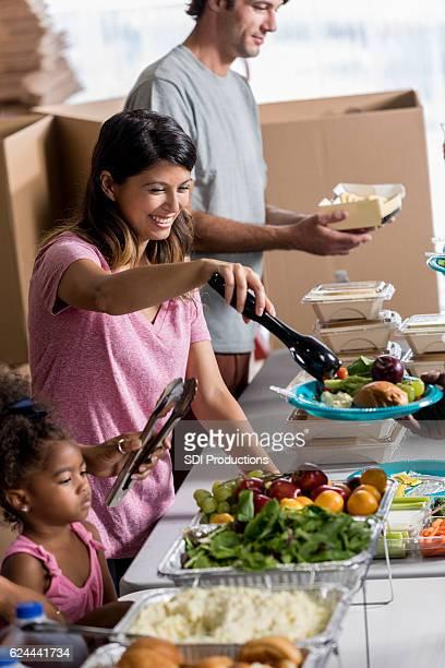 Confident Hispanic woman volunteering at soup kitchen