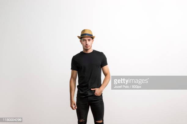 a confident hispanic young man with hat and black t-shirt in a studio - zwart shirt stockfoto's en -beelden