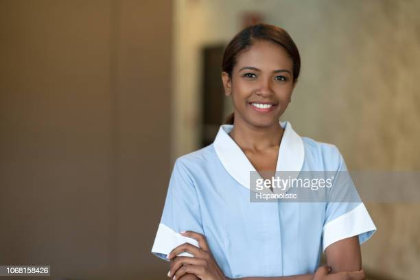 Confident hotel maid looking at camera smiling with arms crossed
