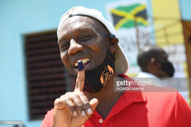 Confident Hugh Graham representing the Peoples National Party shows his finger with ink at the polling station in Cotton Piece, where he cast his...