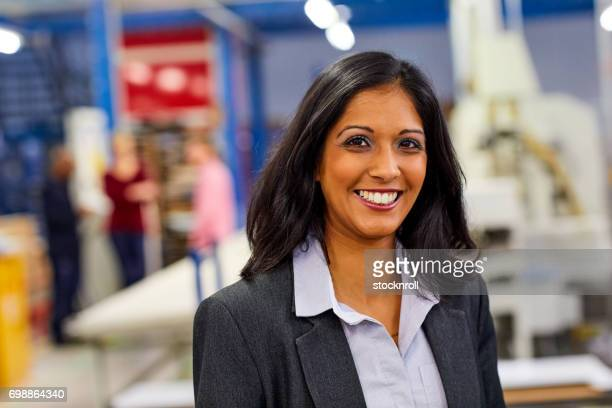 confident indian businesswoman standing in factory - indian woman stock photos and pictures