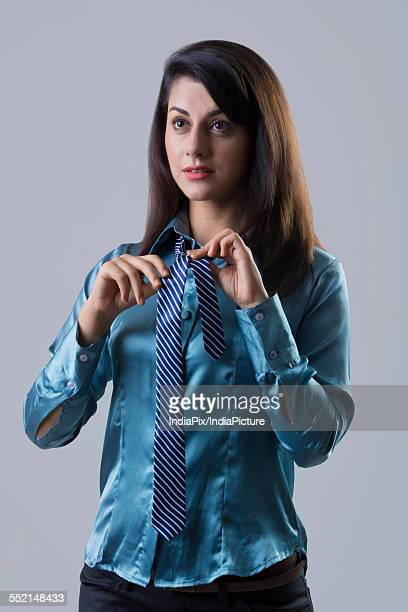 Confident Indian businesswoman wearing tie against gray background