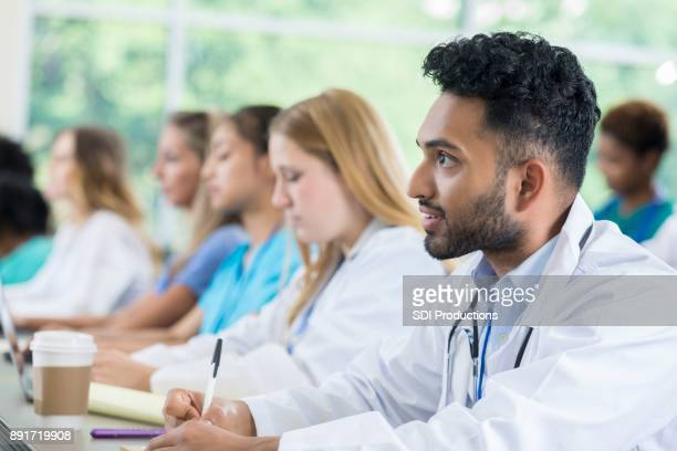 Confident Indian medical student taking notes during a lecture