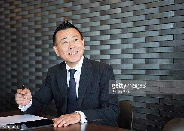 Confident Japanese businessman making notes, smiling