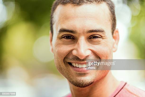 Confident jogger smiling in park