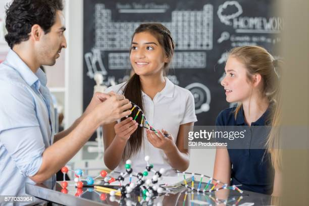 confident junior high teacher works with students in science lab - junior girl models stock pictures, royalty-free photos & images