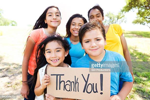 Confident kids in the park with 'Thank You!' sign