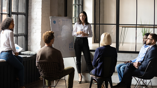 Confident lady business trainer coach give flip chart presentation 1182967368