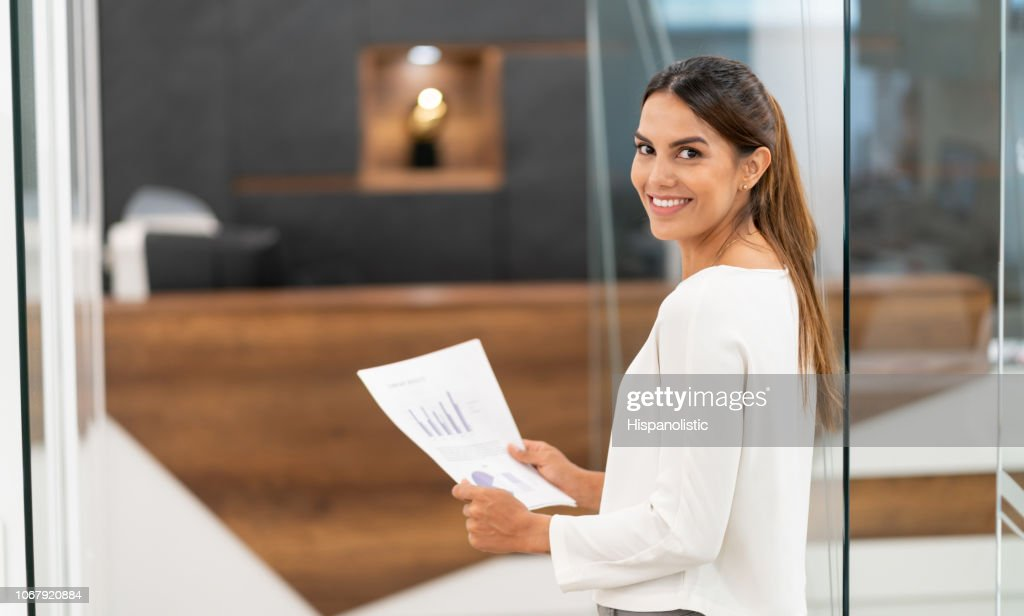 Confident latin american businesswoman at the office smiling at camera while holding documents : Stock Photo