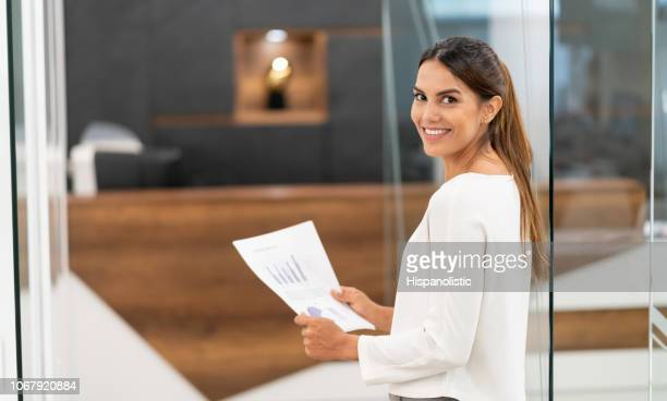 Confident latin american businesswoman at the office smiling at camera while holding documents