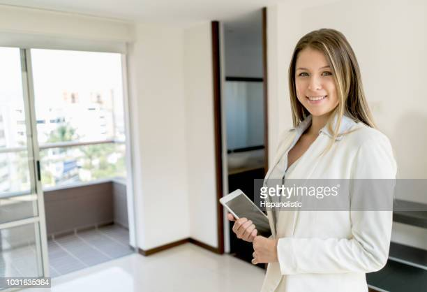 confident latin american real estate agent at a property looking at camera smiling - real estate broker stock photos and pictures