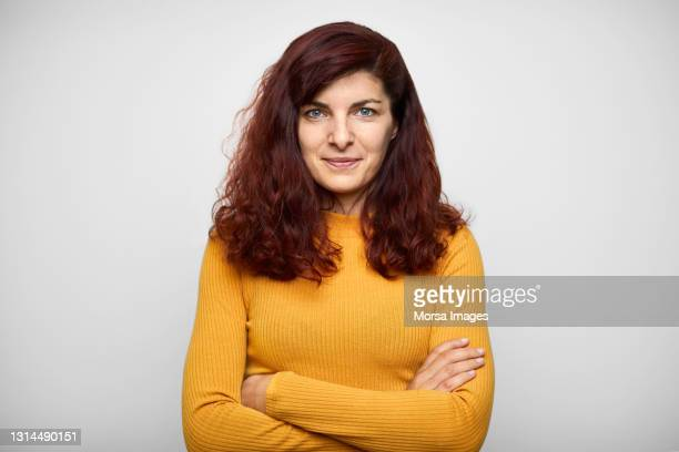 confident latin american woman against white background - redhead stock pictures, royalty-free photos & images