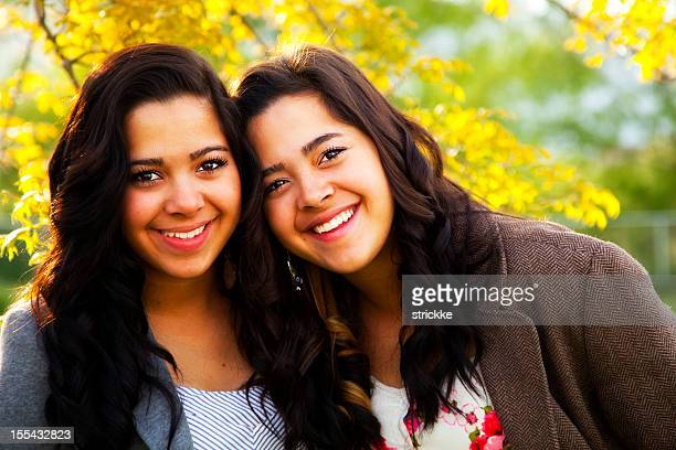 confident latina twins in colorful, natural setting - sister stock photos and pictures