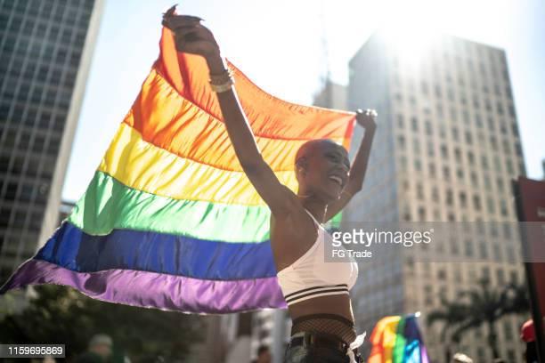 mulher lésbica confiável que prende a bandeira do arco-íris durante a parada do orgulho - desfiles e procissões - fotografias e filmes do acervo